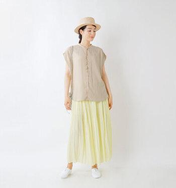 アイボリーカラーのフレンチスリーブブラウスに、薄いイエローのプリーツスカートを合わせたコーディネートです。全体的に淡いカラーをチョイスして、夏らしいナチュラルな着こなしに。ハットや素足に白シューズを合わせることで、涼しげにまとめています。