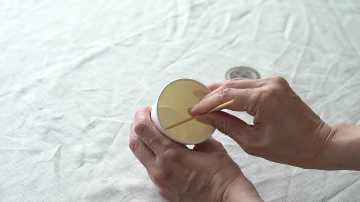 150ml紙コップの底の中心に竹串で穴を開け、芯を底から1cm出るように通し、テープで留めます。 (土台となるキャンドルの型を作る)