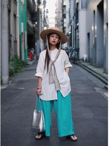 白のオーバーサイズシャツにぎゅっと映える、鮮やかなグリーンのリネンパンツ。バンドカラーのカチッとした印象と、ボリューミーなフォルムと、グリーンのポップさ。ハットのリボンがアクセントになって、視線がパンツだけに向かないバランスもさすがの優秀コーデです。