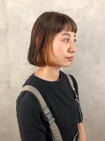 前髪と顔の周りにオレンジのインナーカラーを入れたボブヘアです。