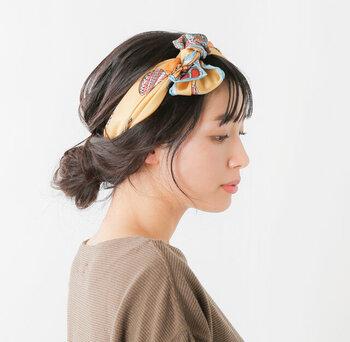 髪を下ろした状態で後頭部を覆うように下からスカーフをヘアバンドのように結び、ローシニヨンでまとめたアレンジ。トップの髪の毛をふんわり引き出すのがポイントです。