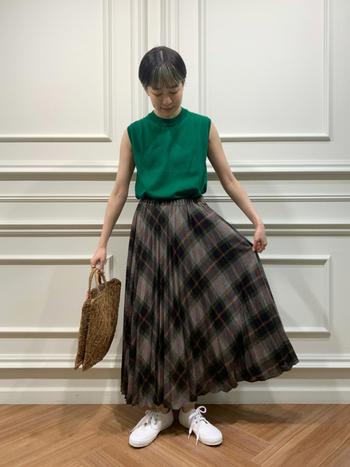 渋めのトーンのチェック柄プリーツスカートに、深みのあるグリーンのタンクトップ。軽やかだけど、秋色効果が効いています。