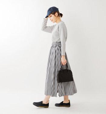 チェック柄のスカートに、グレーのトップスをタックインしたコーディネートです。スニーカー風のスリッポンとトートバッグは黒系で色を揃えて、大人カジュアルなコーディネートに。ネイビーのキャップはスカートと色味を合わせることで、全体的にまとまりのある着こなしに仕上げています。