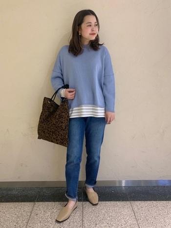 ブルーの長袖トップスに、デニムパンツを合わせた同系色コーデ。トップスの裾からボーダートップスをチラ見せして、ワンアクセントをプラス。アニマル柄のトートバッグが派手な印象になり過ぎないよう、足元はベージュのスリッポンでシンプルにまとめています。