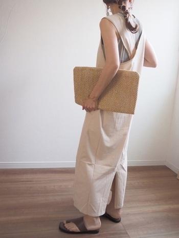 背面のクロスデザインが印象的なロングワンピースに、ストライプ柄のインナーを仕込んだ爽やかな装い。ペーパー素材のバッグで夏らしい雰囲気を高めています。