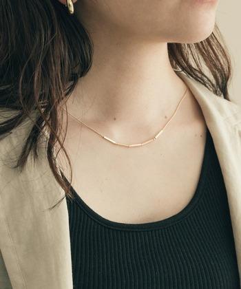 黒のインナーにベージュのジャケット。胸の開いたトップスにゴールドの華奢なバーネックレスがさらりと映えます。5つにわかれたバーモチーフが肌に吸い付くようなデザインで大人っぽい。