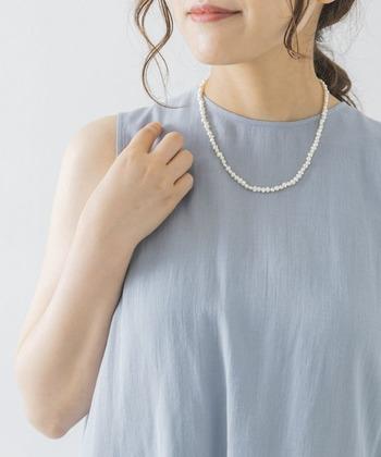 お呼ばれにぴったりな爽やかブルーのノースリーブワンピース。それぞれ形の異なった不思議な魅力の淡水パールネックレスが、表情豊かにコーデをスタイルアップさせてくれますよ。