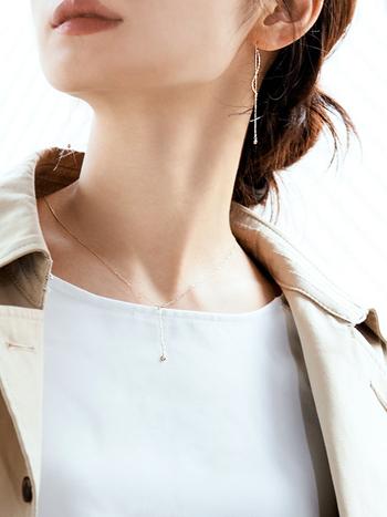 白インナーにベージュジャケットの定番スタイル。華奢なチェーンの先に小さな一粒のダイヤが揺れるピアスとネックレスが、さりげない華やかさをプラスしてくれます。