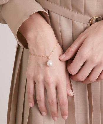 繊細なチェーンと大粒淡水パールのブレスレット。ベージュのプリーツドレスと肌の色、チェーンのゴールドが馴染む中、ひとり凛と美しく佇み純白の輝きを放つパールが上品です。