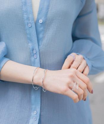 涼しげなブルーのシアーシャツ。それぞれ形の違う華奢なシルバーバングルが、さらに清涼感を増してくれます。夏のオフィスコーデにもぴったり。