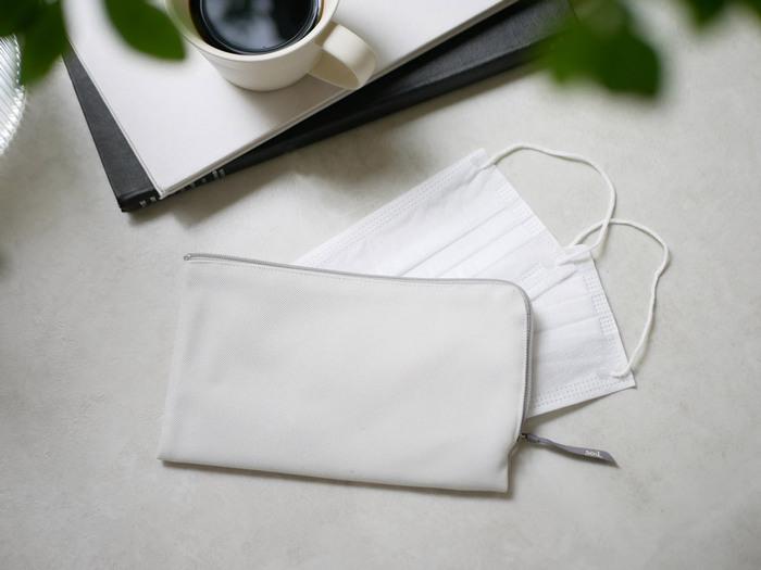 長財布のようにファスナーがL字に開き、出し入れがしやすいマスクポーチです。付属の吸湿脱臭剤を内部の専用ポケットに入れることで、マスクを清潔な状態で持ち運ぶことができます。仕切りがあるので未使用と使用済に分けて収納が可能。2つ折りにすることもできるので、小さめバッグのコーディネートの日も使えます。