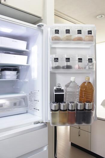 冷蔵庫を開くと、きれいに並べられた容器がずらり。上段には和風だしやコンソメ、乾燥わかめなど、下段には酒や酢、しょうゆなど油分のない調味料があり、どれも使用頻度が高いものばかりで出しやすくなっています。黒いラベルがわかりやすいのにおしゃれで便利。