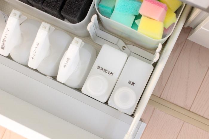 キッチン内でよく使う洗剤もシンクの引き出しへ収納。上から見えるようにラベリングすることですぐに取り出せます。食器用洗剤や万能な重曹は、入浴剤の詰め替えボトルに入れることで、スプーンで計量する手間が省けて時短に。