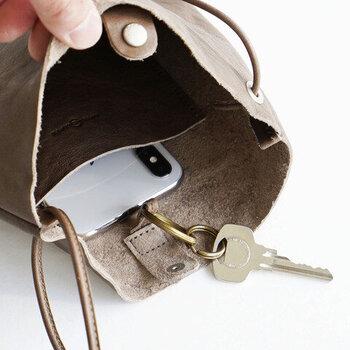 スマホやお財布など必要最低限のものが収納できるサイズ感。口元に革のループが付いているので、リングを通して鍵を付けるなどアレンジして使うことができます。