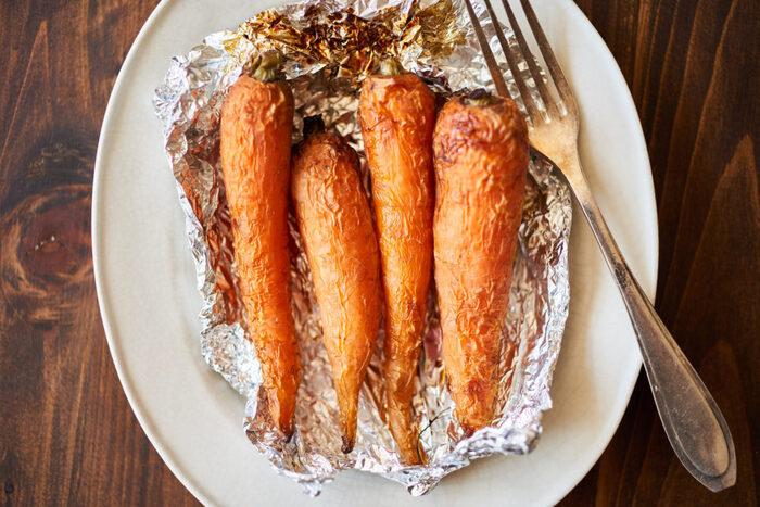 にんじんをアルミホイルで包んでオーブンで焼くだけという、とてもシンプルな1品です。焼いているあいだに、ほかの作業ができるのがオーブン料理のいいところ。じっくりと焼かれたにんじんは、甘みが強くて食べ応え充分です。
