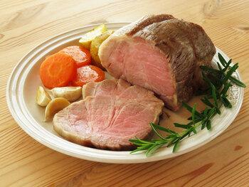 豚肩ロース肉のブロックを、赤ワインやローズマリーなどを加えたブライン液に2晩じっくりと漬け込んでいます。低温のオーブンで1時間程度焼き、アルミホイルに包んでしばらく休ませれば完成。しっとり柔らかなロゼ色のローストポークです。