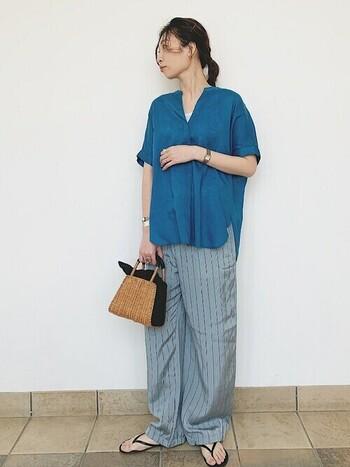 ブルーのシャツ×グレーのストライプパンツで、清涼感のあるコーデ。小さなかごバッグもポイントになっています。