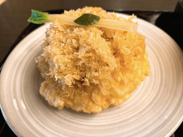せいろうそばに合わせたいのが、もうひとつの名物「天たね」です。元々は天ぷら蕎麦の具でしたが、お客さんがお酒の肴に食べるるようになったことから単品でも提供されるようになりました。こんもりと厚みのある天ぷらに、芝海老が隠れていて風味と食感をプラスしています。