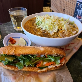 フランスパンに香草やハムなどを挟んだベトナム風サンドイッチの「バインミー」。こちらのお店では特注パンに、レバーやなますなどをたっぷり挟んでいます。ランチでは、蒸し鶏や魚介などのフォーと組み合わせたセットがおすすめ。ベトナム出身のシェフが作るお料理は、どれも本格的です。