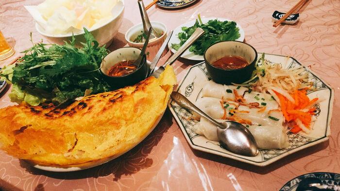 土日祝日は、お昼からアラカルトメニューが注文できますよ。こちらはベトナム南部のホーチミンでよく食べられる「バイン・セオ」。香ばしい皮の中には、もやしや豚肉、小海老などがぎっしり入っています。ベトナム版のお好み焼きのようなもので、野菜がたっぷり食べられると女性に人気です。野菜と一緒に、ヌクマムで作った甘酸っぱいタレをかけていただきましょう。