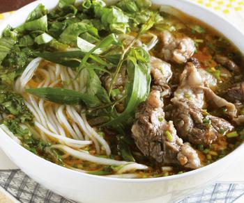 """平日ランチ限定の「牛すじ入りレモングラス風味の辛口麺」は、本格的な味わいが人気です。ベトナム中部の伝統料理で""""ブン・ボー・フエ""""と呼ばれます。干し海老や牛肉の旨みたっぷりのスープは辛口で、あとをひくおいしさ。プルプルの牛すじにレモングラスの香りが爽やかです。"""