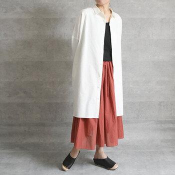 赤のワイドパンツに、黒のトップスをタックインしたモード感のあるコーディネート。白のシンプルなロングシャツを羽織って、印象的なカラーを少し抑えめに見せているのがポイントです。足元も黒シューズで落ち着いた印象に。夏のカラフルコーデを秋に着まわしするなら、シンプルなロングシャツが大活躍しますね。
