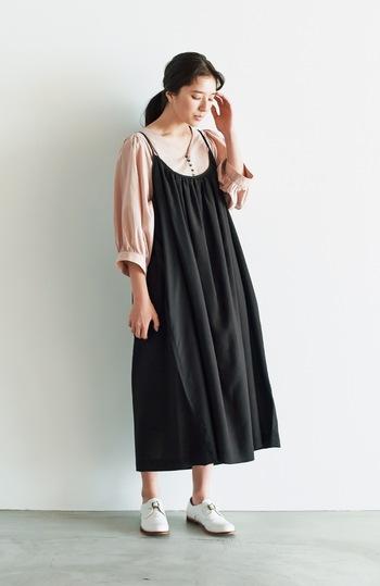 黒のキャミワンピースに、ピンクの七分袖ブラウスを合わせたコーディネートです。黒×ピンクのフェミニンカラーを組み合わせて、シンプルに着こなしています。足元は白のシューズで、爽やかな印象に。上着やカーディガンなどをプラスすれば、秋まで着まわしできるスタイリングですね。