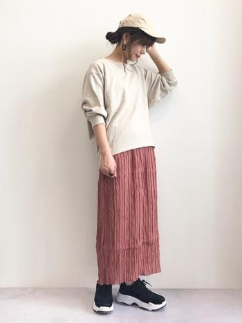 七分袖のスウェットトップスは、秋から冬まで大活躍するアイテム。シワ加工が特徴的なピンクのロングスカートに合わせて、カジュアルながらもガーリーなテイストをプラスしています。ごつめの黒スニーカーとベージュのキャップで、大人カジュアルなスタイリングに。