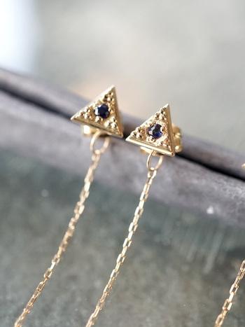 三角のピラミッドデザイン。深い青色に輝くサファイヤのまわりに細かな粒金をあしらったピアスです。キャッチにはチェーンがついていて、耳の後ろから下がるようになっているのも個性的で楽しめます。