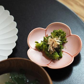 華やかな梅のデザインが施された伝統ある有田焼の小皿です。5枚の花弁が捻るように描かれた祥瑞(しょんずい)模様は、昔から縁起の良いものとして親しまれてきました。  縁の部分は少し立ち上がっているので、まるで梅の花に包まれているようなイメージで使えるのがおすすめポイント。優しいピンクと花弁を縁取る朱赤の線がかわいいですよね。