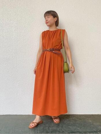 オレンジのワンピースは可愛くなりすぎないので、大人にも着こなしやすいアイテム。ブラウンのベルトでウエストマークすれば、また違った表情の着こなしに。