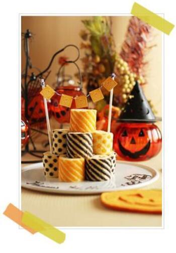 ブラックココアパウダーで黒、アイシングカラーでオレンジに着色したハロウィンらしいロールケーキタワー。糸とケーキピックで作ったガーランドをロリポップ棒に巻き付けて、デコレーションします。