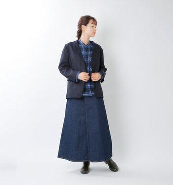ブルーのチェック柄シャツに、ダークネイビーのジャケットを合わせた着こなし。ボトムスはデニムのログスカートで、全体を同系色でまとめています。黒のブーツで季節感をプラスしつつ、さりげない引き締めポイントとしても活用。大人のデイリーコーデにぴったりな、ジャケットスタイルです。