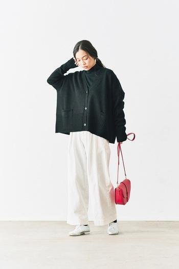 黒のゆったりカーディガンに、黒のハイネックを合わせたスタイリング。ボトムスは白のワイドパンツで、シューズも白で色を合わせています。上下で白黒がはっきりと分かれた、マネしやすいモノトーンスタイルですね。赤のショルダーバッグが、よい差し色になっています。