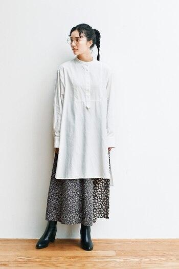 白のロングシャツに、花柄のスカートを合わせたコーディネートです。黒地のスカートに白で花柄をあしらったデザインは、シックな印象のモノトーンコーデに華やかさをプラスしてくれます。足元は黒のブーツで、季節感とクールさをアピール。