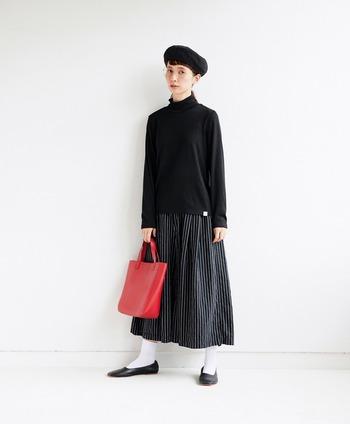 黒のタートルネックに、白黒のストライプ柄スカートを合わせたコーディネート。白靴下に黒パンプスで、とことんモノトーンにこだわったスタイリングです。赤のトートバッグが、ダークトーンに映えますね。