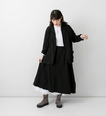 白のワンピースに、黒の吊りスカートをレイヤードしたコーディネート。裾からワンピースをチラ見せすることで、シックなスタイリングの中にさりげないガーリーさを演出しています。スカートと同素材の黒ジャケットをプラスして、メリハリのあるモノトーンコーデに。