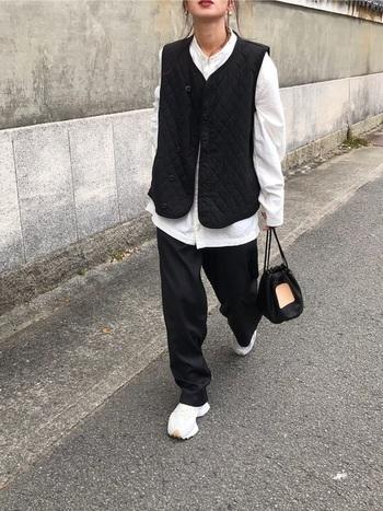 白のシャツに黒のベストを合わせたコーディネート。パンツとバッグは黒で、白のスニーカーを合わせたモノトーンスタイルです。白の分量が少なめなので、ベストはあえて前を開けてバランスをとっているのがポイント。