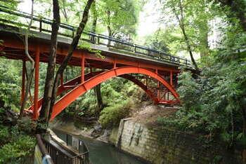 """渓谷の入口にかかる橋は""""ゴルフ橋""""と呼ばれています。昭和初期に、この付近に大きなゴルフ場があったことが由来。緑に映える真っ赤な橋が印象的ですね。"""