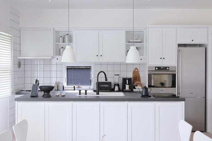 賃貸物件に付いているイメージが強い吊り下げ収納ですが、デザイン次第では海外風のおしゃれなキッチンに。  こちらはモノトーンでまとめられたスタイリッシュなキッチン。キッチン家電も壁面収納の一部に組み込んだ海外仕様です。  見せる収納として吊り下げ戸の扉取り付けず遊び心を残しています。