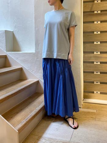 くすみ系の水色と青色スカートのコントラストがお互いの良さを引き立てるリラクシーなコーディネート。一見シンプルですが、ランダムにギャザーが入ったスカートは動きがあり、女性らしいシルエットに見せてくれています。