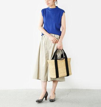青色にベージュのフレアパンツを合わせた軽やかスタイリング。程よく立ち上がったモックネックがカジュアルさを和らげ、大人の女性らしさを印象づけています。リラクシーな夏を演出してくれるかごバッグも素敵。