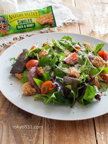 シリアルバーと粉チーズの塩気のきいたご馳走サラダ*ドレッシングは不要でオリーブオイルをかけてシンプルに。シリアルバーをサラダに加えることで、たんぱく質や食物繊維などの栄養素を手軽に摂取できるのも嬉しいポイント。