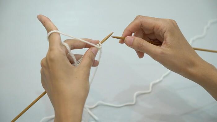 ①2本の棒針から1本を抜く ②ハの字で持つ ③作り目の手前の糸を人さし指にかける ④右手の針を作り目部分に針を通す ⑤糸をかけて、中指で糸を下に押す ⑥目を抜くと1目めが完成 ⑦左の目も外す ⑧裏目が1段完成