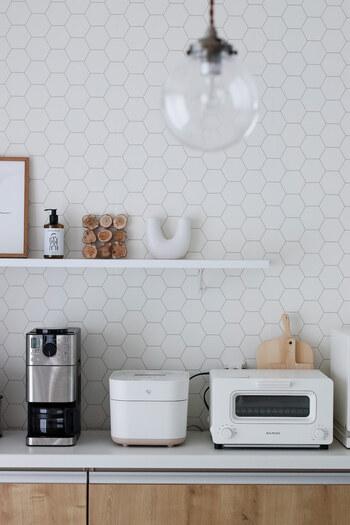 白、黒、ナチュラルブラウンでまとめられた北欧テイストのキッチン。ハニカム柄の壁紙は自分で張り替えたそう。  カップボードの上にはデザイン性の高いキッチン家電を置き、その上に取り付けた棚板にお気に入りの雑貨を飾っています。  キッチンの壁に飾り棚を取り付けて、お気に入りのインテリアを楽しむ空間にしてみては?