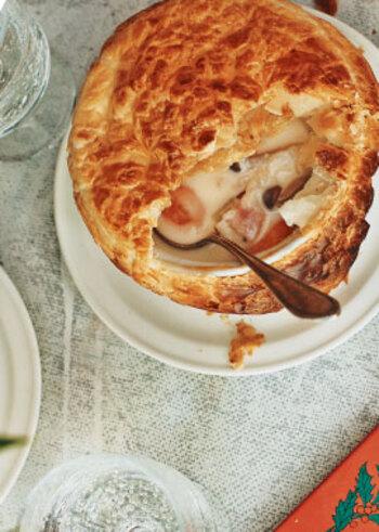 ベーコンや野菜などを炒めたら小麦粉をふり入れ、牛乳を少しずつ注いで煮ます。冷めたら、市販のパイシートをかぶせてオーブンで焼くとリッチなシチューポットパイの完成。ホワイトソースをわざわざ作る必要もなく意外と簡単です。