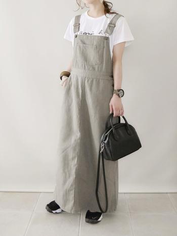 グレージュのサロペットスカートのインナーにも使いやすい、シンプルな白のロゴTシャツ。カジュアルな中にも女性らしい雰囲気を演出できる、大人可愛いレイヤードスタイルです。小物は黒でまとめてスッキリと。