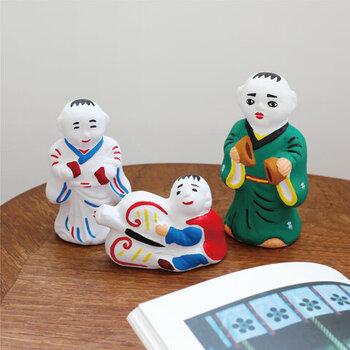お人形は、素朴で親しみを覚える表情です。お饅頭を持ったお人形は、子供の健やかな成長を願って作られています。