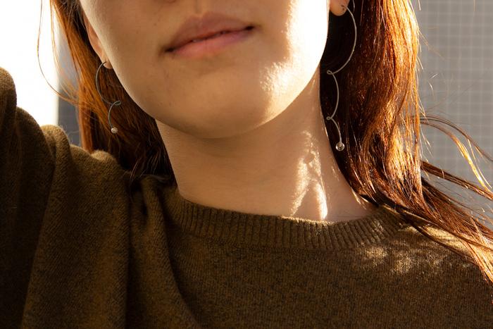 くるんくるんの曲線が楽しい、なんともユニークなピアス。金属に糸を巻き付けて作られています。髪を下ろしているときに付ければ、躍動感あるフォルムが髪の隙間から覗いて可愛いこと間違いなし。細いピアスですが、ほどよく目立ってくれます。