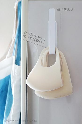 すっきりとしたホワイトの大きめフック。実は、ダイソーの「マグネットボディタオルハンガー」をタテにして使っています!横にしてボディタオルをかけるためのアイテムを、マスク収納に活用したアイデア。深さがあるため、布マスクを複数かけられて◎。玄関ドアに貼りつけておくと便利ですね。